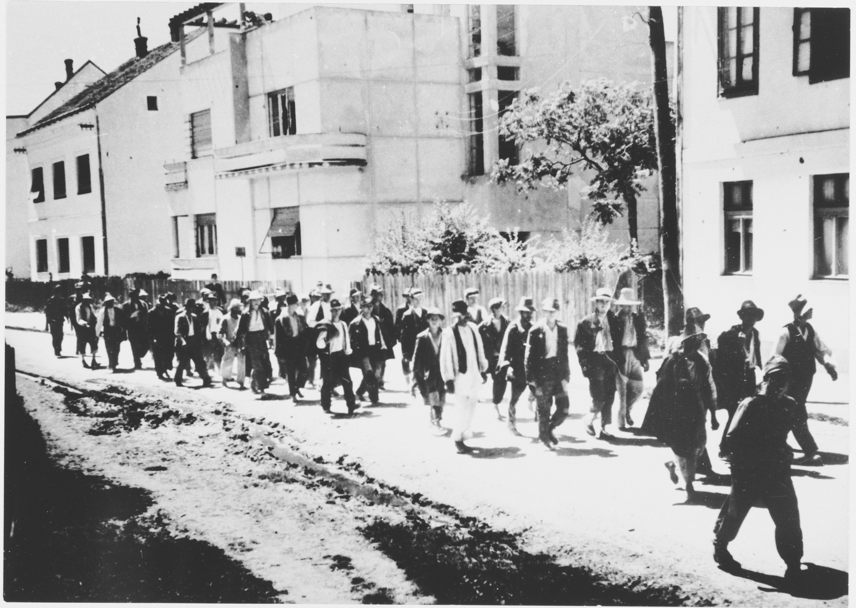 [Probably Serbian villagers from the Kozara region who have been rounded-up for deportation, marching in a column under Ustasa guard through the streets of a town.]