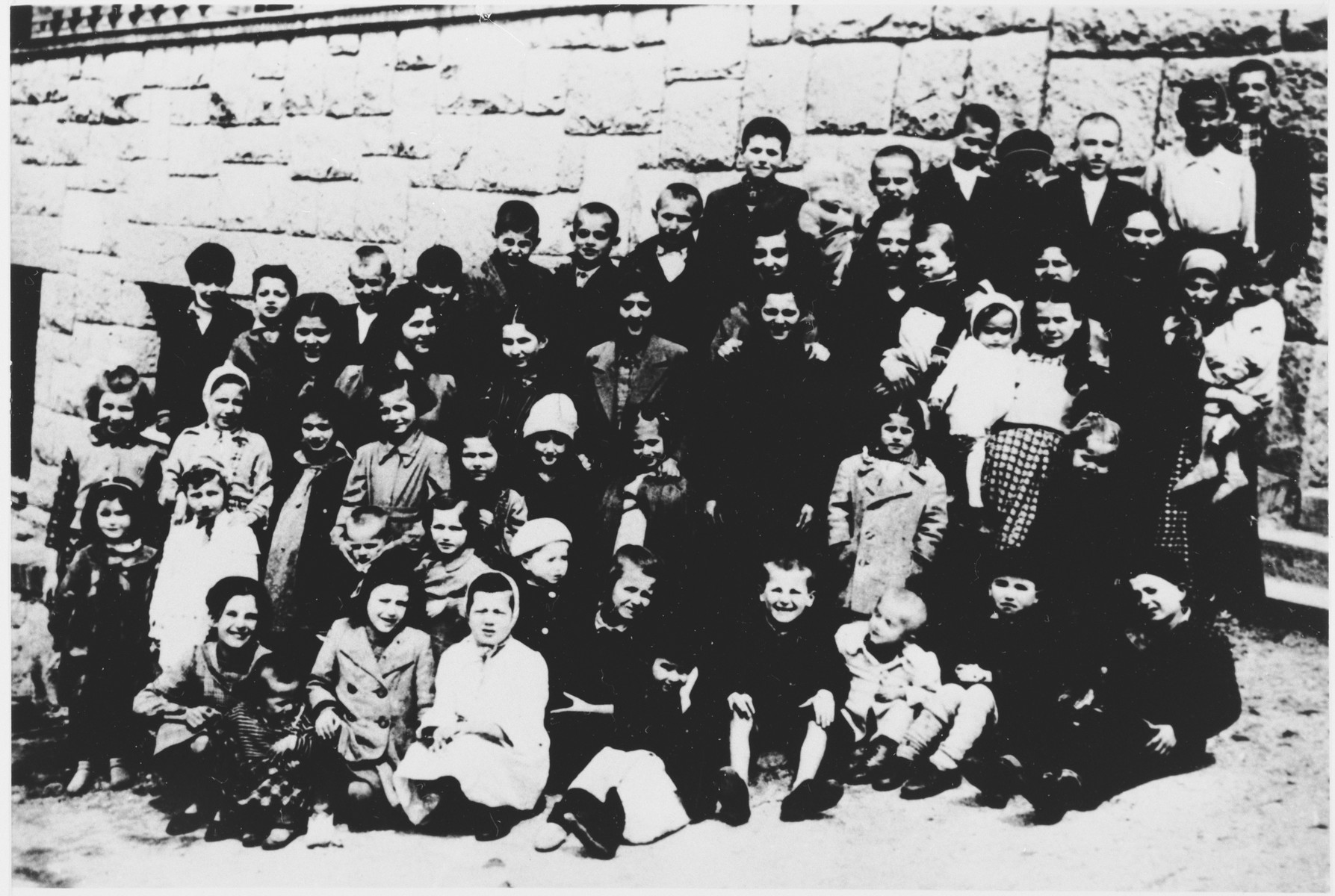 Group portrait of children who are being separated from their mothers by Ustasa guards, at the entrance to the Stara Gradiska concentration camp.