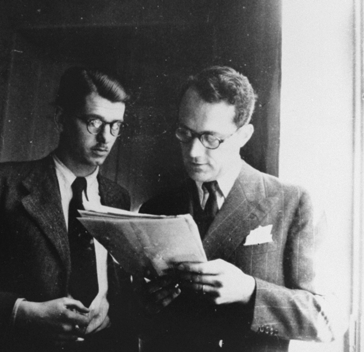 Varian Fry (right) shows a document to his associate, Daniel Benedite, in the offices of the Centre Americain de Secours.