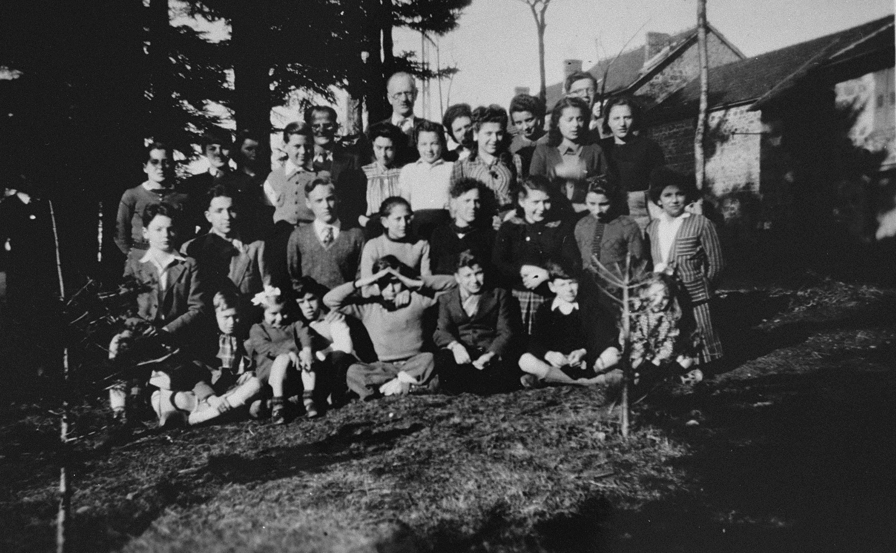 Group portrait of Jewish and non-Jewish refugee children sheltered in various public and private homes in Le Chambon-sur-Lignon during World War II with some of the French men and women who cared for them.  Among those pictured are: Pastor André Trocmé (top row, center wearing glasses), Daniel Trocmé (top row, right, partially hidden), Edouard Theis (top row, to the left of André Trocmé), Peter Feigl (third row from the front, second from the left), Amede Dutry (third row from the front, far left), Kurt Grossman (second row from the front, far left), Jean Speigel (second row from the front, second from the left), and Simone Fullenbaum (second row from the front, far right).