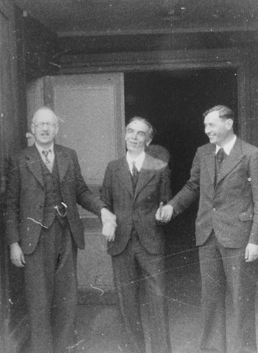 Pastor André Trocmé (left), Roger Darcissac (center), and Pastor Edouard Theis (right) pose at the entrance to the church in Le Chambon after their release from the Saint-Paul d'Eyjeaux internment camp.
