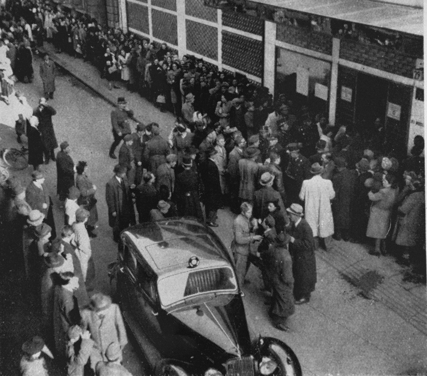 Police attempt to control the crowd of Jews, who are waiting outside a branch of the Swiss legation located in the Glass House on Vadasz Street hoping to obtain Schutzbriefe that would protect them from deportation.  In the foreground is the car used by Vice Consul Carl Lutz.