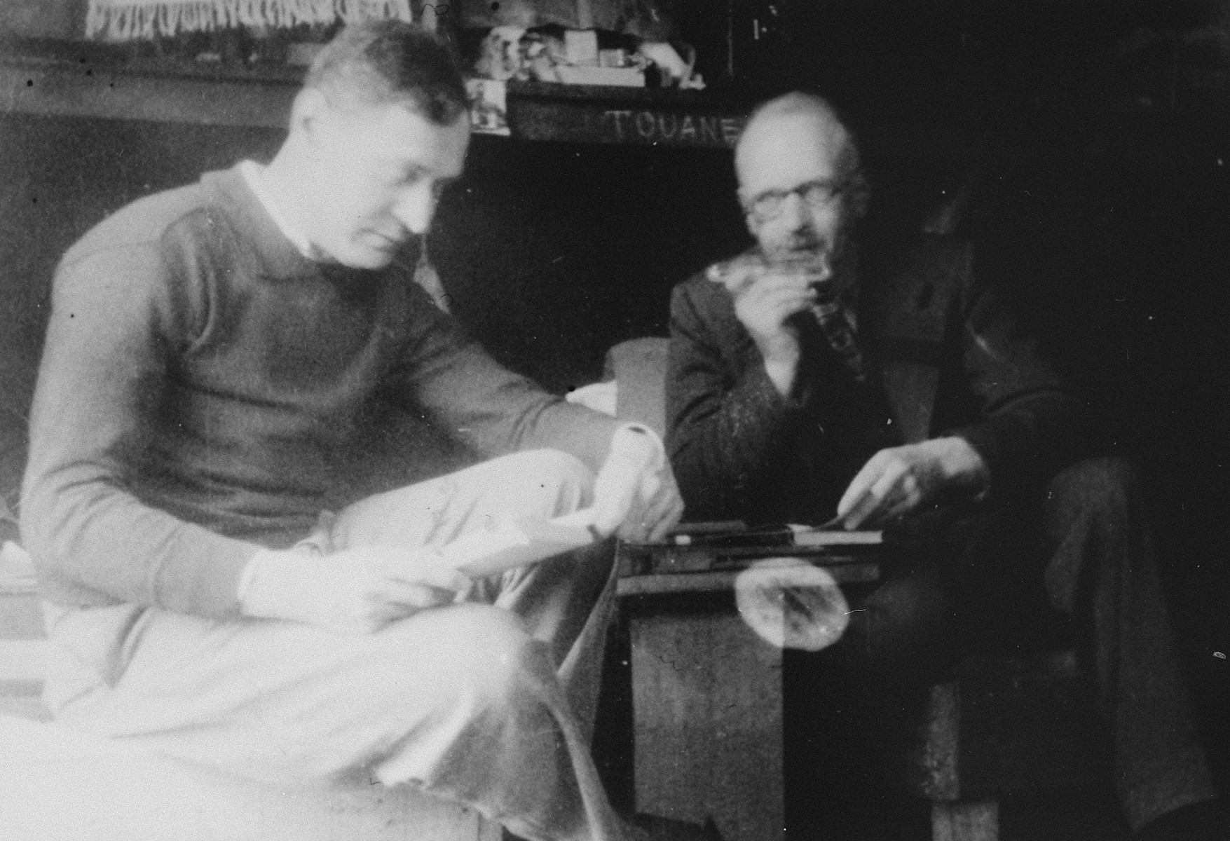 Pastors André Trocmé and Edouard Theis entertain themselves during their imprisonment in the Saint-Paul d'Eyjeaux internment camp.  Trocmé (right) plays the harmonica while Theis (left) reads a book.