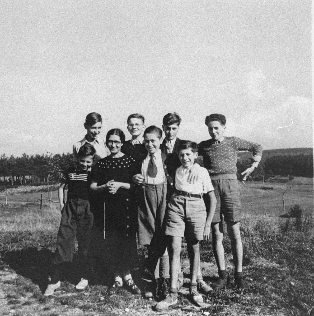 Juliette Usach poses with a group of Jewish youth who are living at the La Guespy children's home in Le Chambon-sur Lignon.  This is one photo from an album presented to Elizabeth Kaufmann prior to her departure from the La Guespy refugee home in Le Chambon-sur-Lignon.    Founded in 1941 by the Secours Suisse aux enfants and run by Juliette Usach, the La Guespy children's home provided shelter to a number of Jewish and non-Jewish refugee children who were living in Le Chambon-sur-Lignon during the Nazi occupation.  Among those pictured are Jean Nallet (back row with glasses), Joseph Atlas (back row, third from the left), Victor Atlas (back row, right), Manfred Goldberger and Juliette Usach.