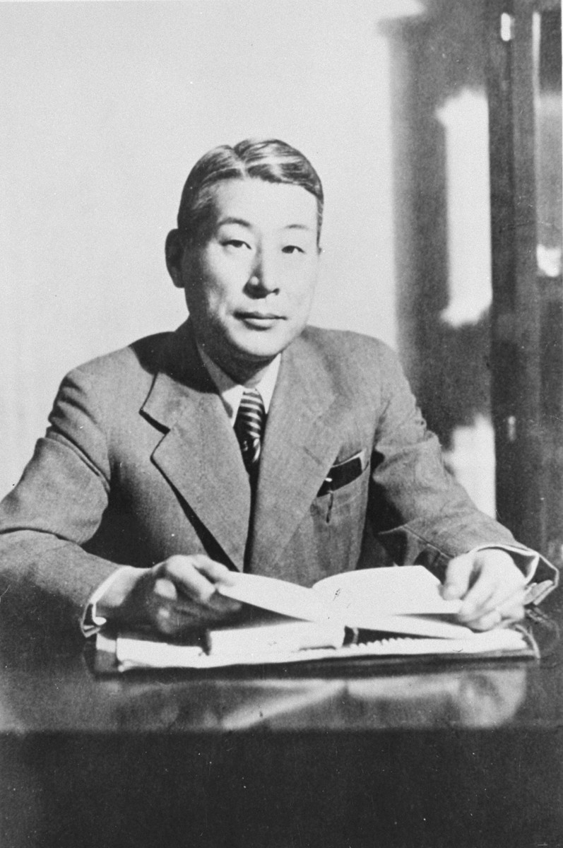 Chiune Sugihara sits behind a desk in his office.