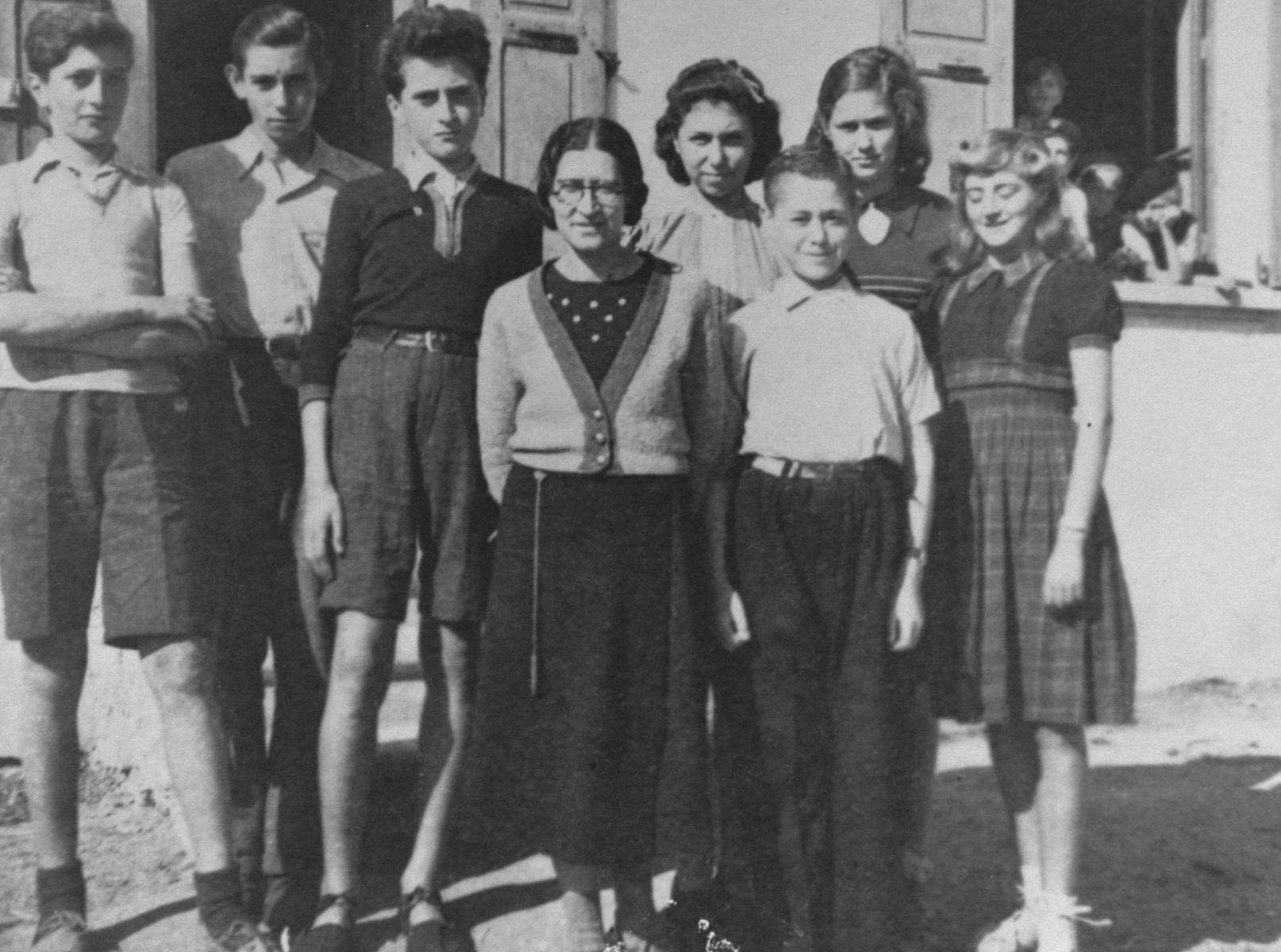 Jewish youth living in the La Guespy children's home in Le Chambon-sur-Lignon, pose with Juliette Usach.   Pictured from left to right are: Joseph Atlas (Poland), Jacob Lewin (Wurzburg), Victor Atlas (Poland), Dr. Juliette Usach (in glasses), Lily Braun, Manfred Goldberger, Hanne Hirsch (Karlsruhe), and Wiltrude Hene (Freiburg).