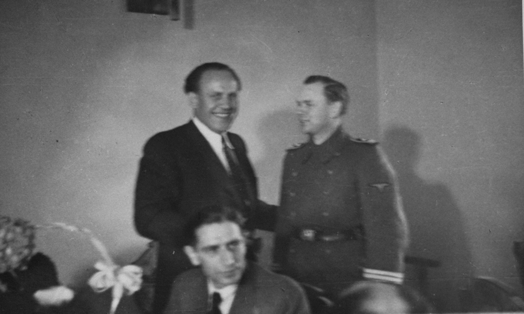 Oskar Schindler at a dinner party in Krakow with an SS officer.    At parties like this, Schindler made contact with various SS and German officials, which often led to tips about impending deportations that enabled him to save his laborers.