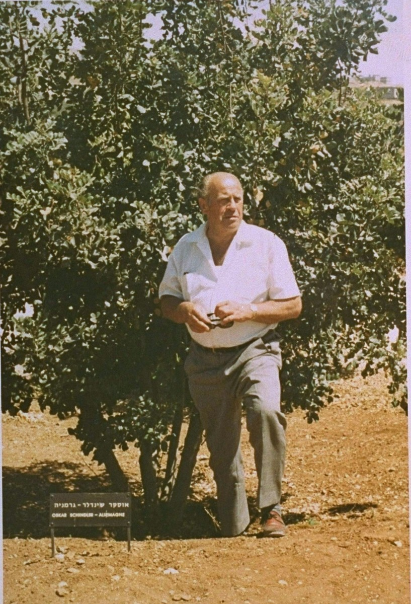 Oskar Schindler poses next to the tree he planted on the Avenue of the Righteous Among the Nations at Yad Vashem.