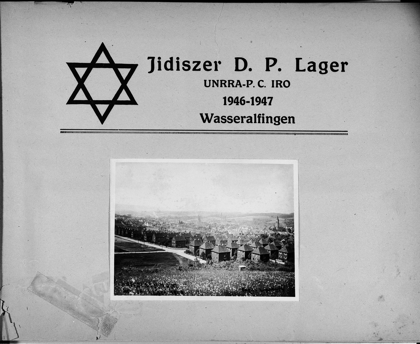 Title page of a presentation photo album of the Wasseralfingen DP camp, illustrated with a photo of an exterior view of the homes in the camp.