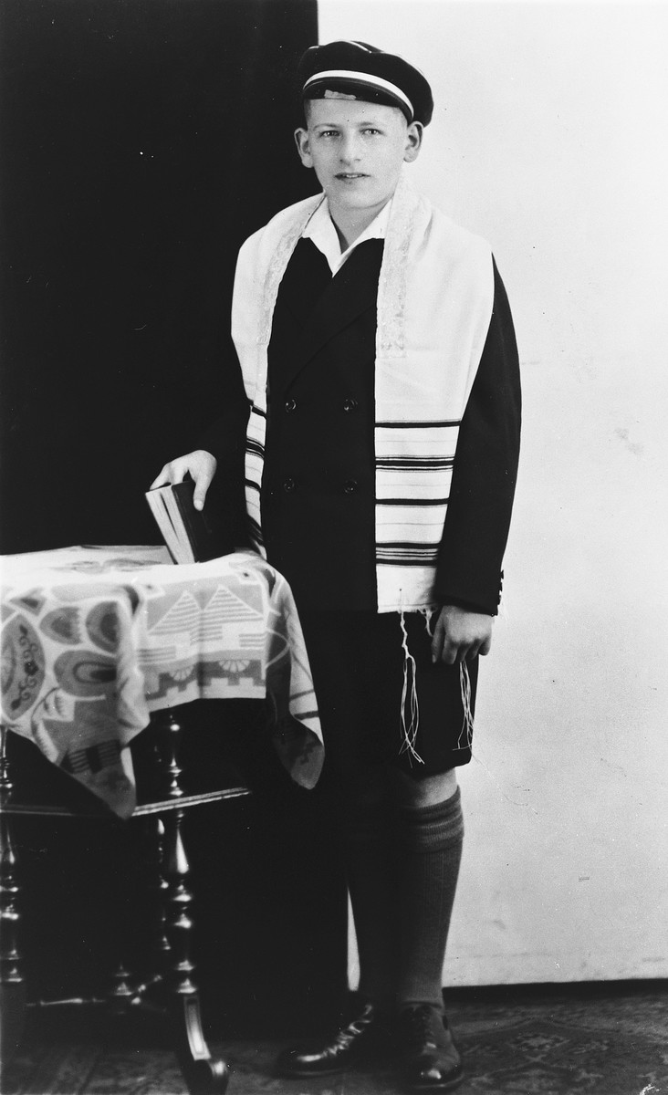 Bar Mitzvah portrait of Richard Bikakes wearing a tallit and holding a prayer book.