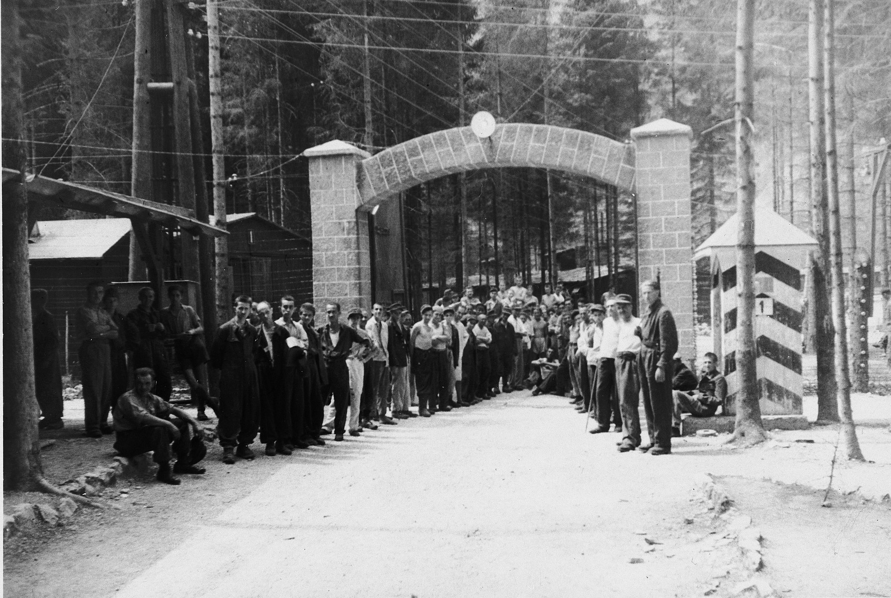 "Survivors of the Ebensee sub-camp gather by the entrance to the camp in preparation for their departure.  The original caption reads: ""Displaced persons at entrance to camp which was their Hell on this earth.  Now the camp holds Hitler's S.S. troops."""