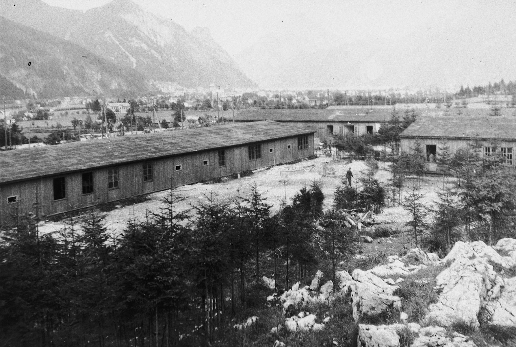 """Exterior view of the barracks of the Ebensee subcamp of Mauthausen.  The original caption reads: """"View of the barracks where the displaced persons lived.  They were allowed only body space and living three high."""""""