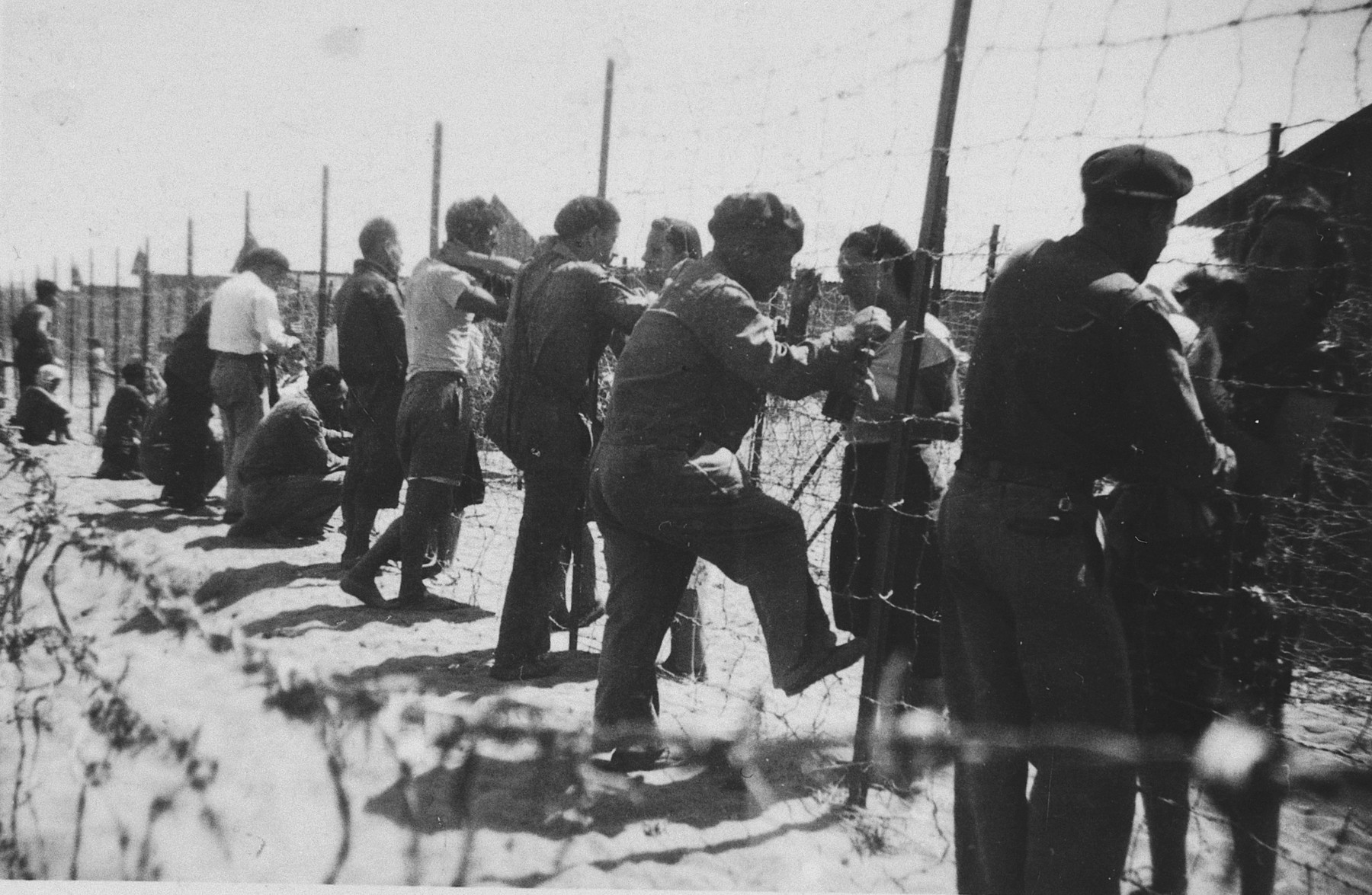 Prisoners gather by the barbed wire fence surrounding the Gurs internment camp.