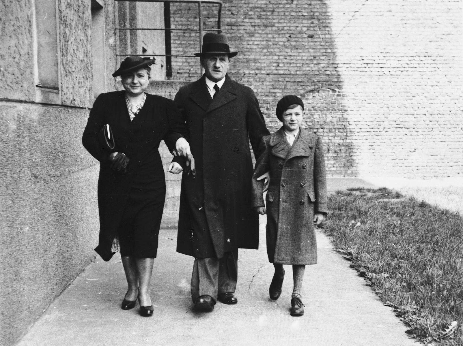 A young boy walks with his parents behind their home on Oderstrasse, prior to his leaving Germany for France.  Pictured (left to right) are Bertha, Salomon, and Norbert Bikales.