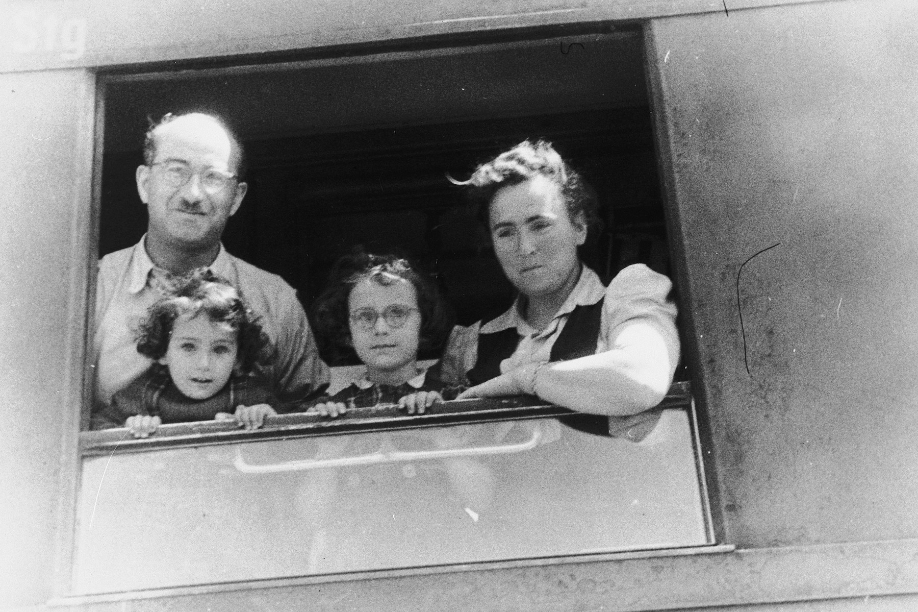 The Slepian family looks out a window of their train while on route to Bremerhaven, where they will board a ship to America.