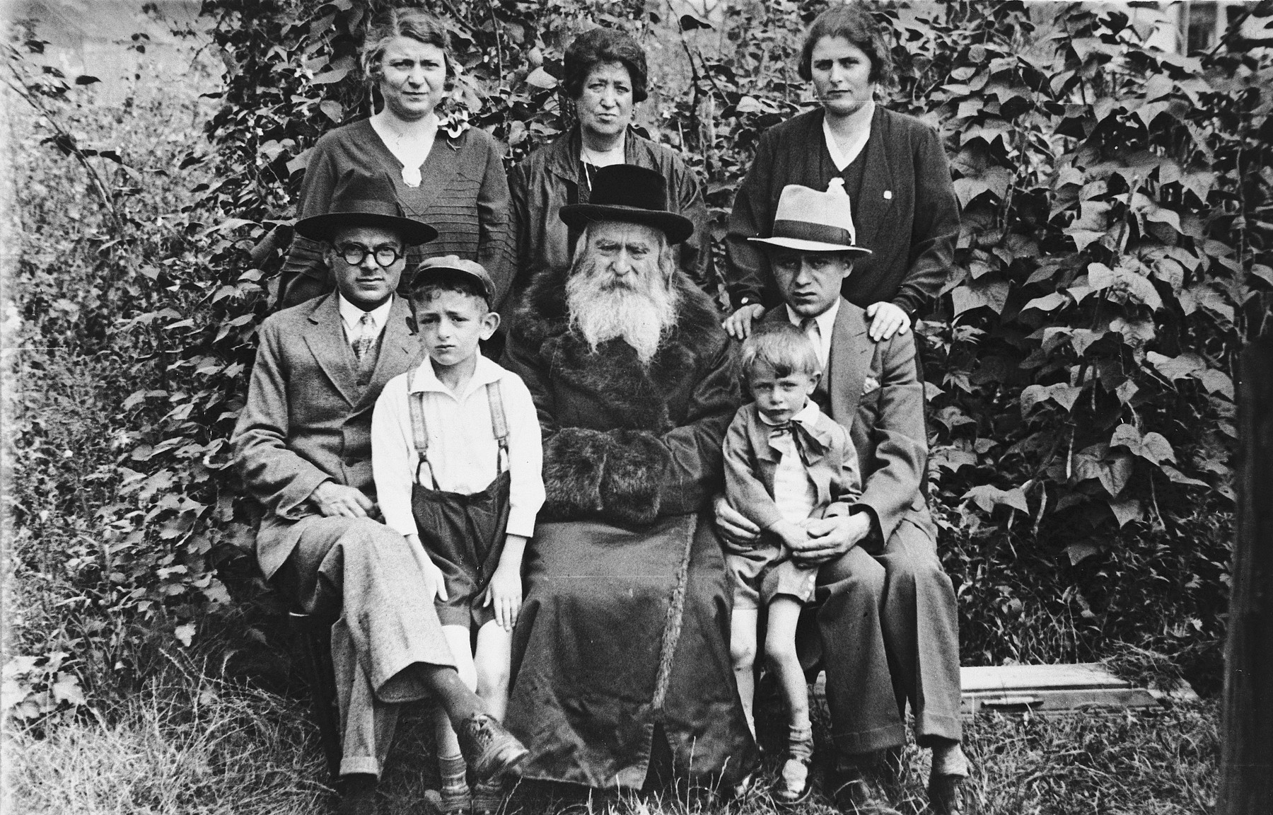 Three generations of a family pose for a group portrait on the occasion of the visit of a son from America.  Pictured in the front row are Moise Bander, a cousin of the donor (name unknown), Rabbi Meir Bander (the donor's grandfather), his son Harry Bander who was visiting from the United States, and Norbert Bikales seated on his lap.  Standing in back are Bertha Bander Bikales, the rabbi's second wife, and Bertha's sister.  Of those pictured only Norbert and Harry survived.