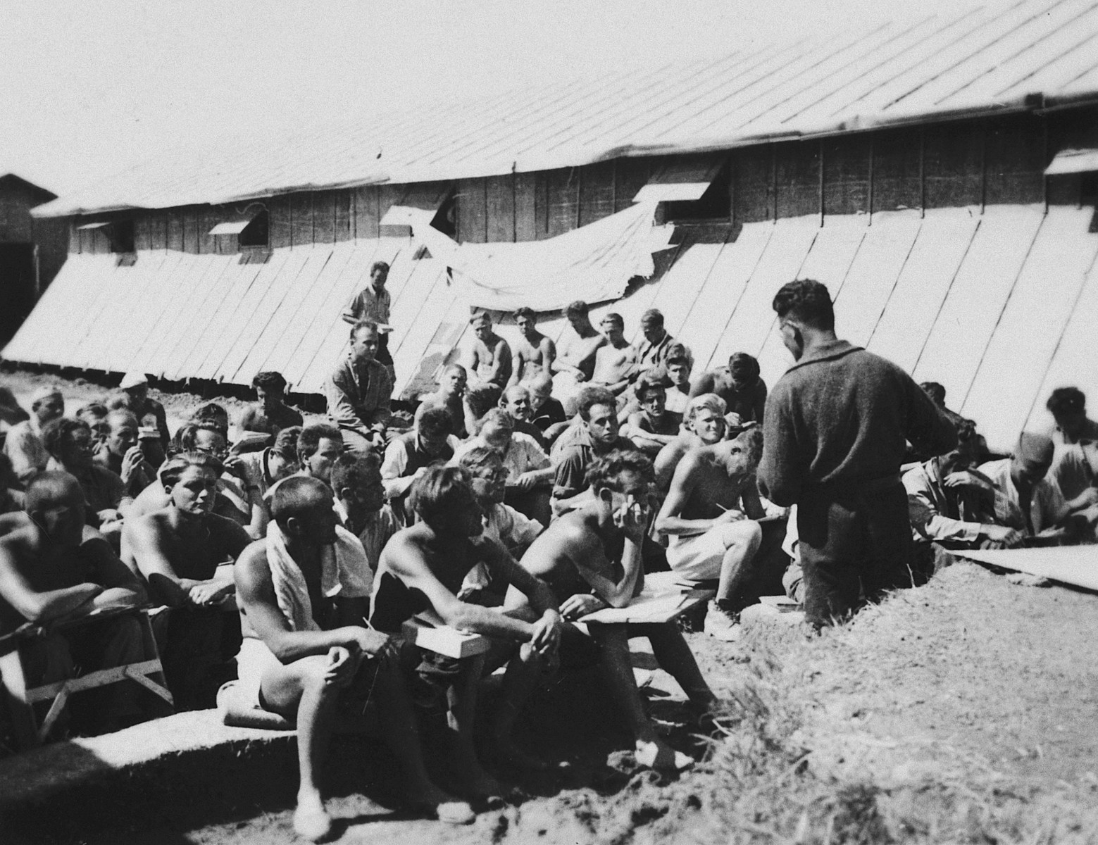 Prisoners listen to a talk in front of the barracks in the Gurs concentration camp in France.