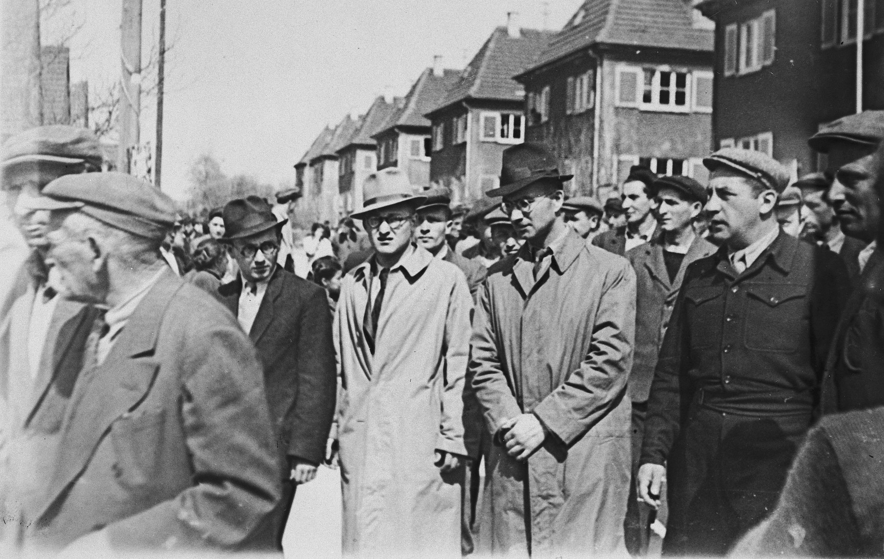 Jewish displaced persons gather on a busy street in the Wasseralfingen DP camp.  Pictured in the dark hat is camp director, Natan Slepian.