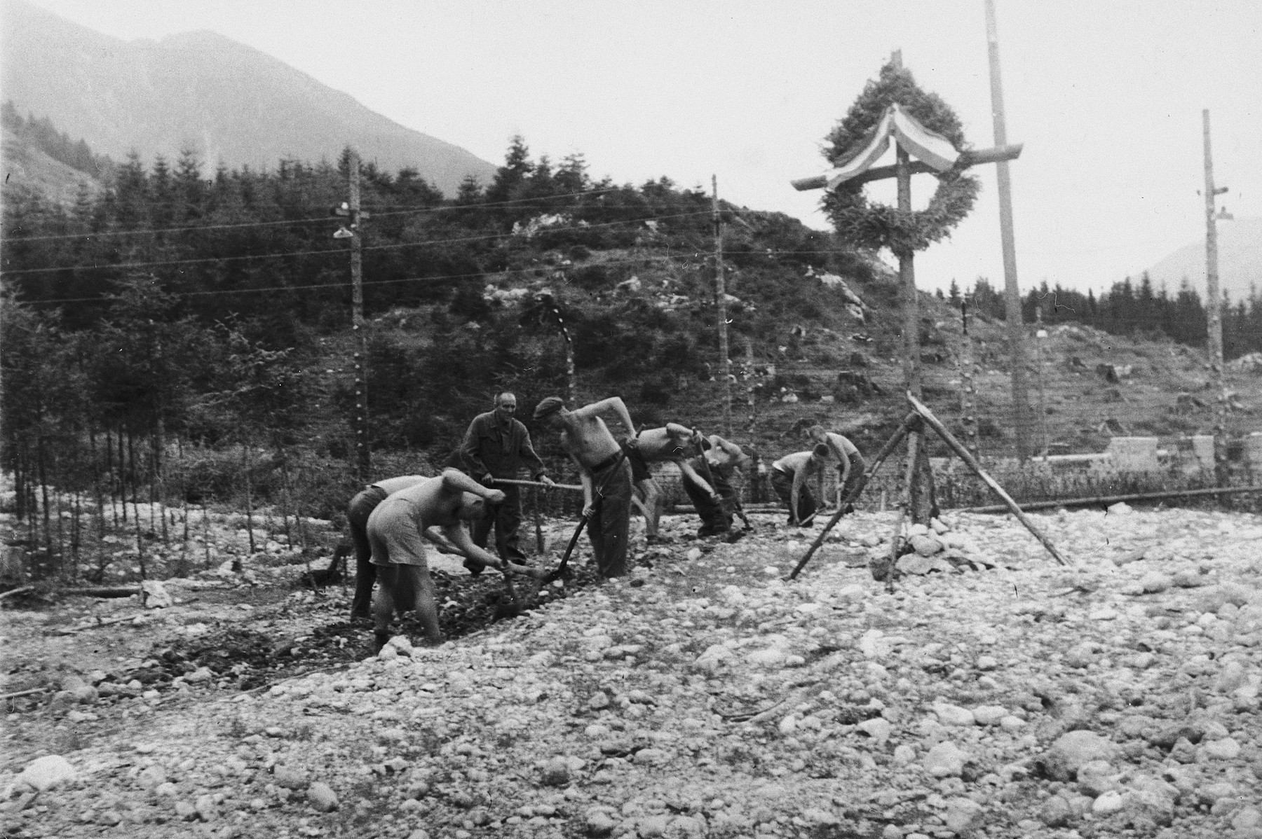 "Survivors or former guards of the Ebensee sub-camp bury the ashes of prisoners who perished there.  The original caption reads: ""Fixing the grave for over 100,000 displaced persons who died and their bodies burned to ashes."""