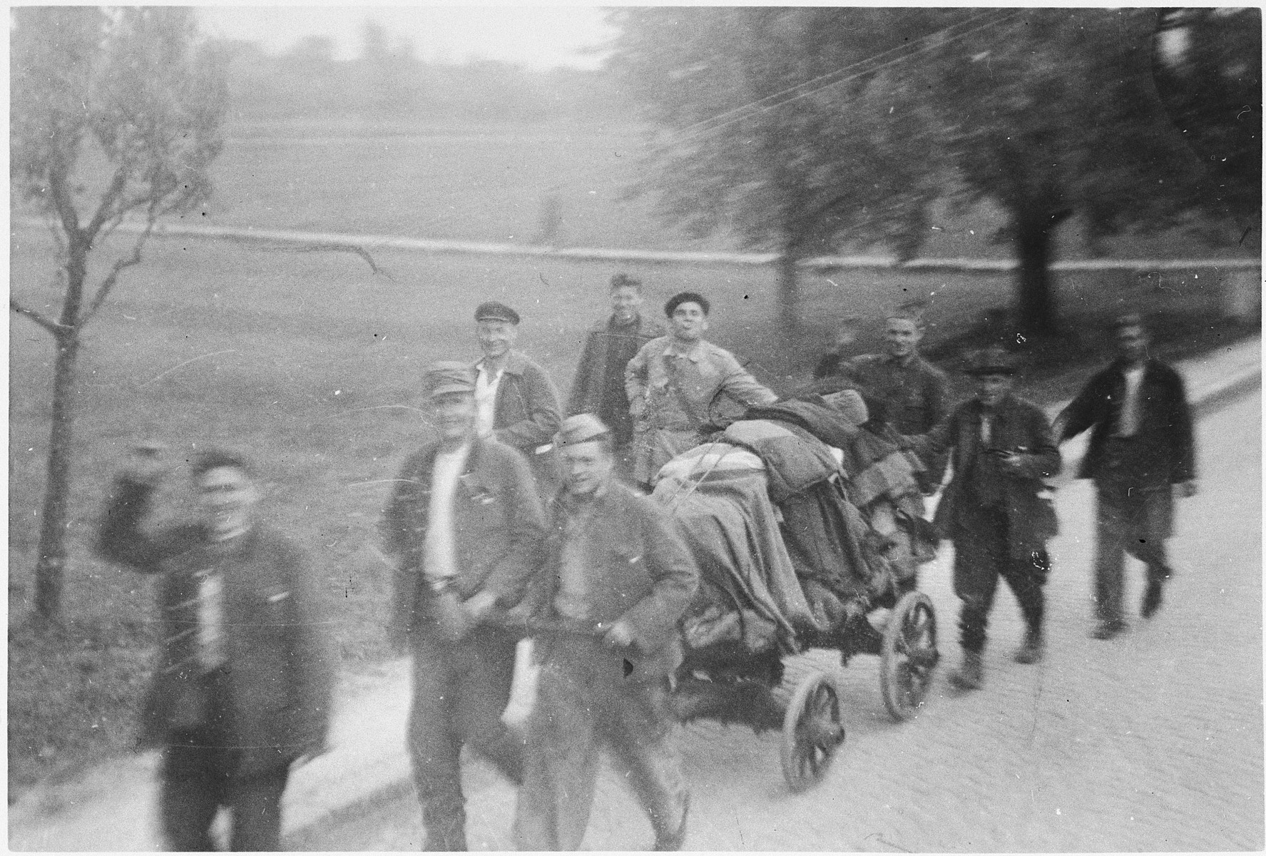 """Jubilant survivors of the Ebensee sub-camp leave the camp with their few belongings.  The original caption reads: """"Forced laborers going home."""""""