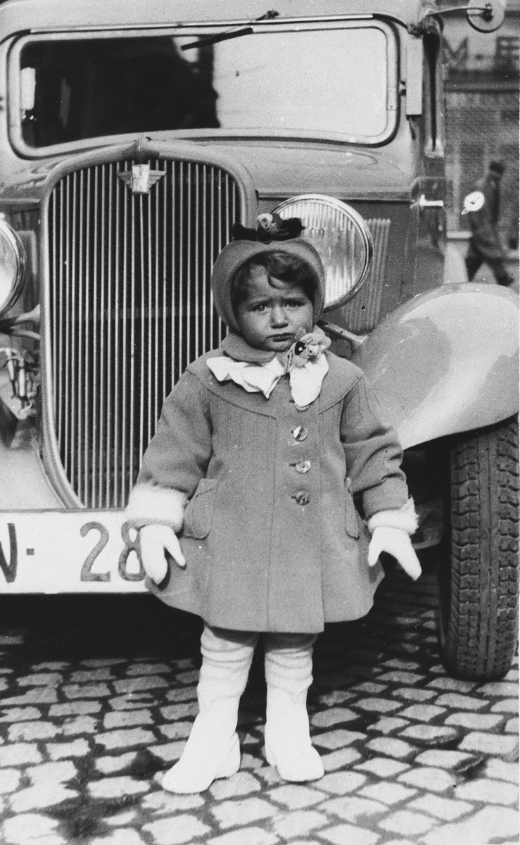 The young step-sister of Natan Slepian poses next to a large automobile.  She and her parents later perished in the Holocaust.