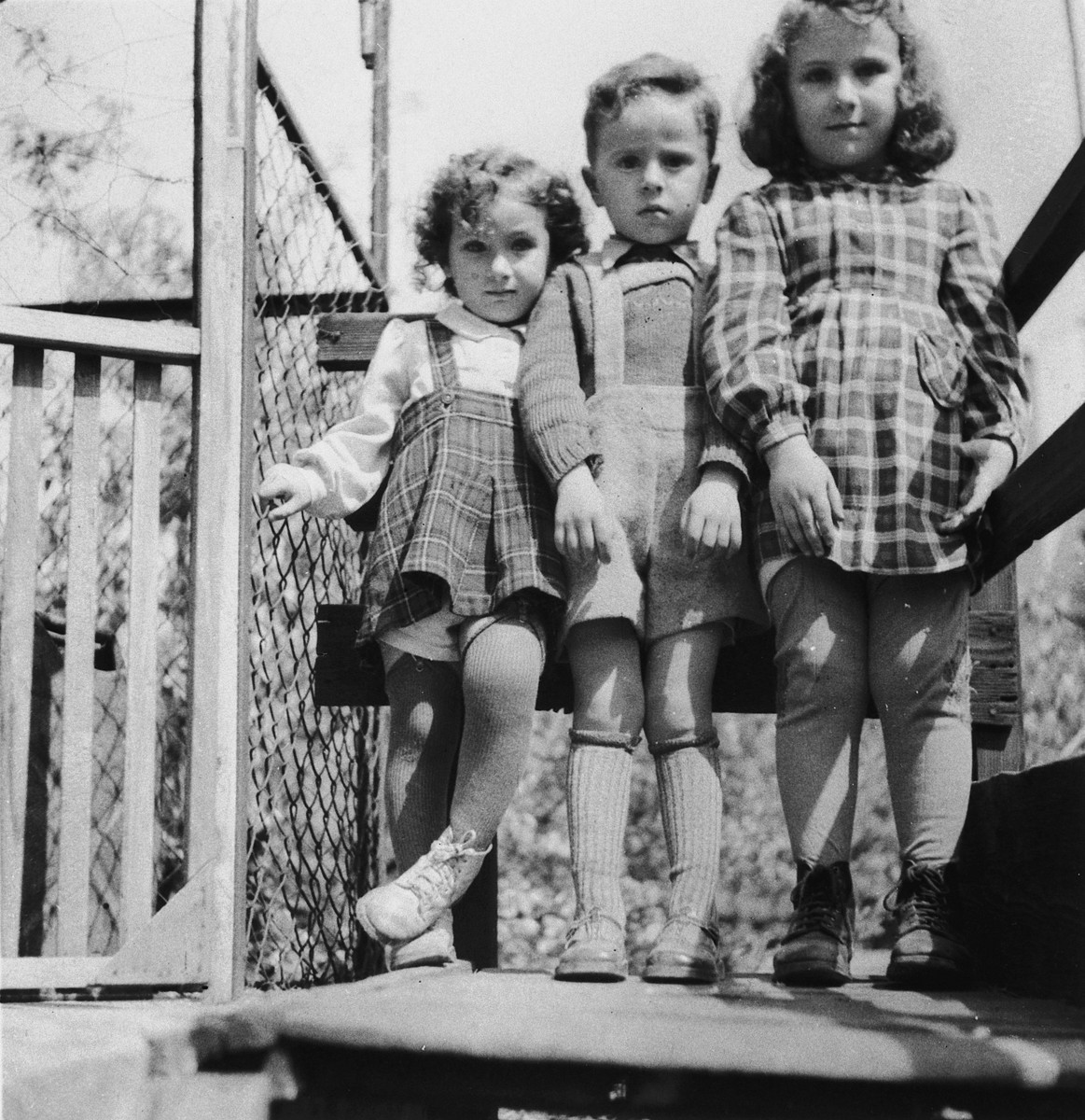 Three young children pose outside next to a fence in the Wasseralfingen DP camp.  Pictured are Pauline, Joseph and Rita Slepian.