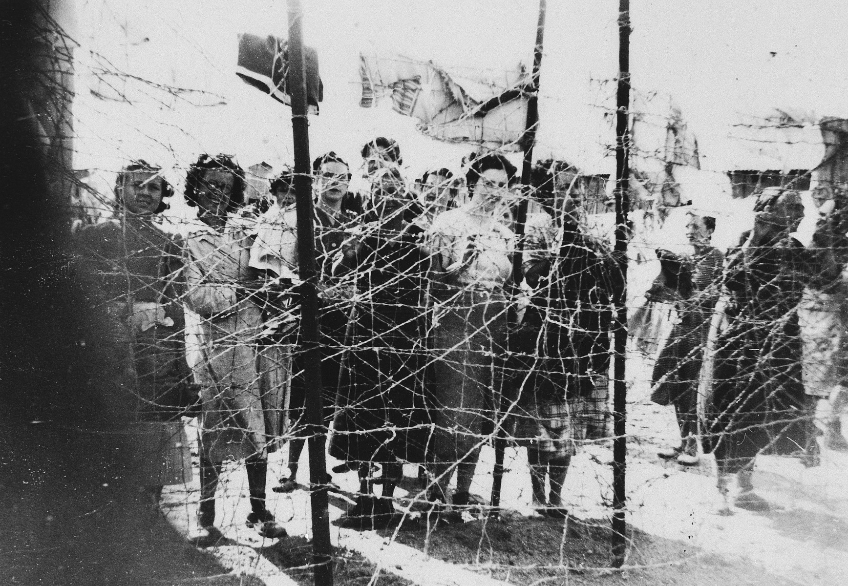 Female prisoners gather by the barbed wire fence surrounding the ...