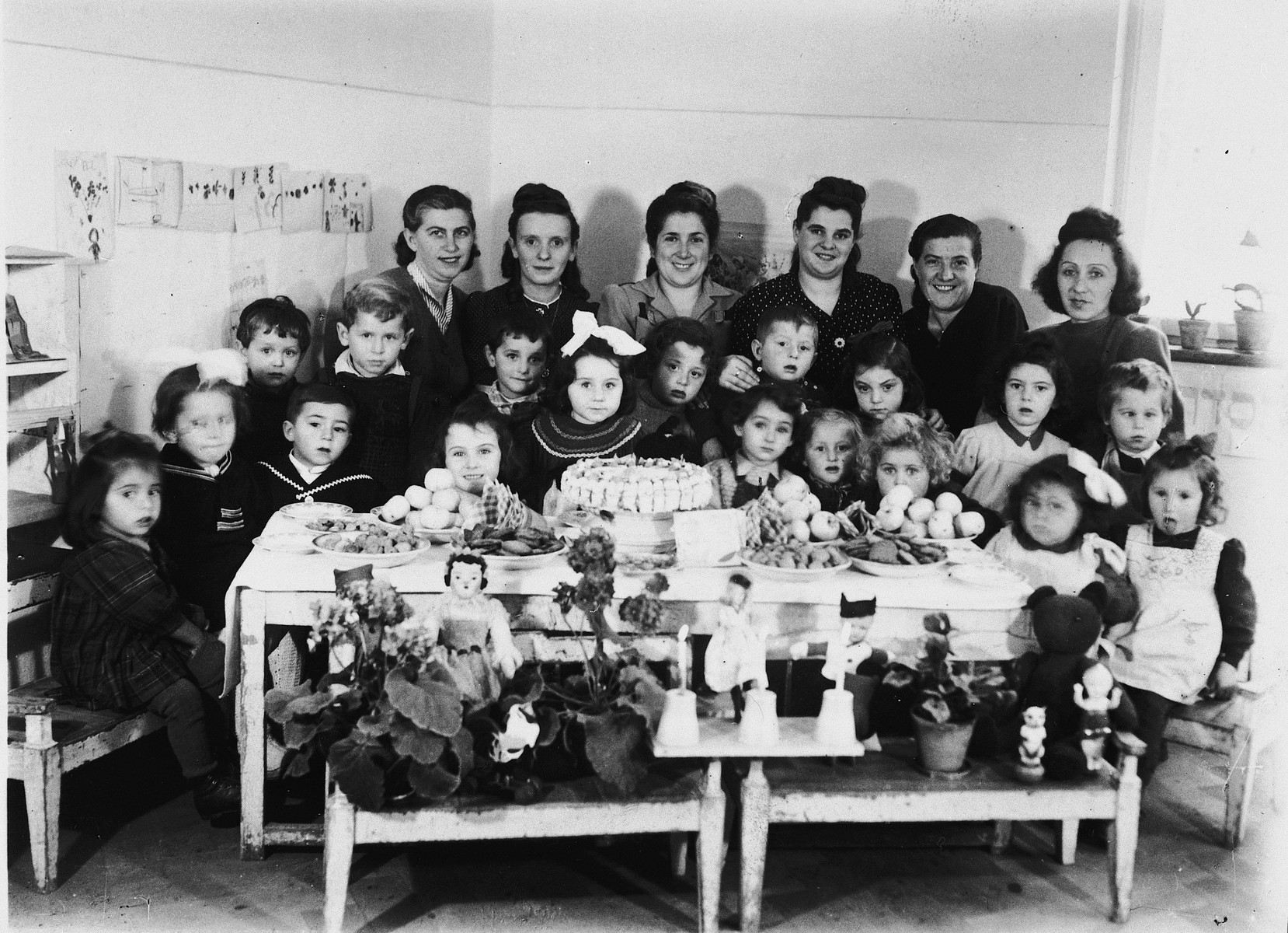 Young children and their dolls gather around a table to celebrate a birthday in the Wasseralfingen DP camp.  Among those pictured is Pauline Slepian.  Also pictured is Fagala Brenner (second row, third from the right).