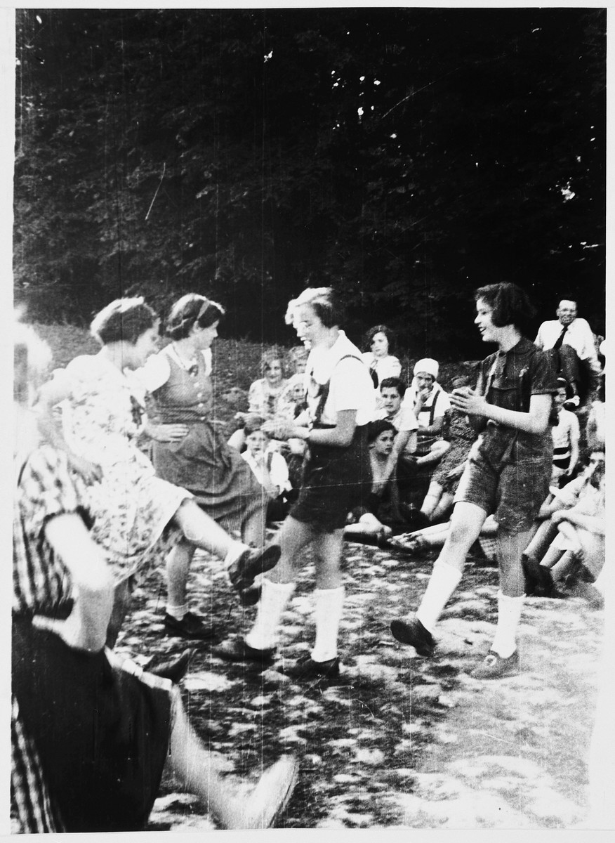 A group of Jewish refugee girls from the Chateau de la Guette OSE [Oeuvre de Secours aux Enfants] children's home dance outside.  Among those pictured is Erika (Fée) Beyth (center) and Renate Tauber (right).