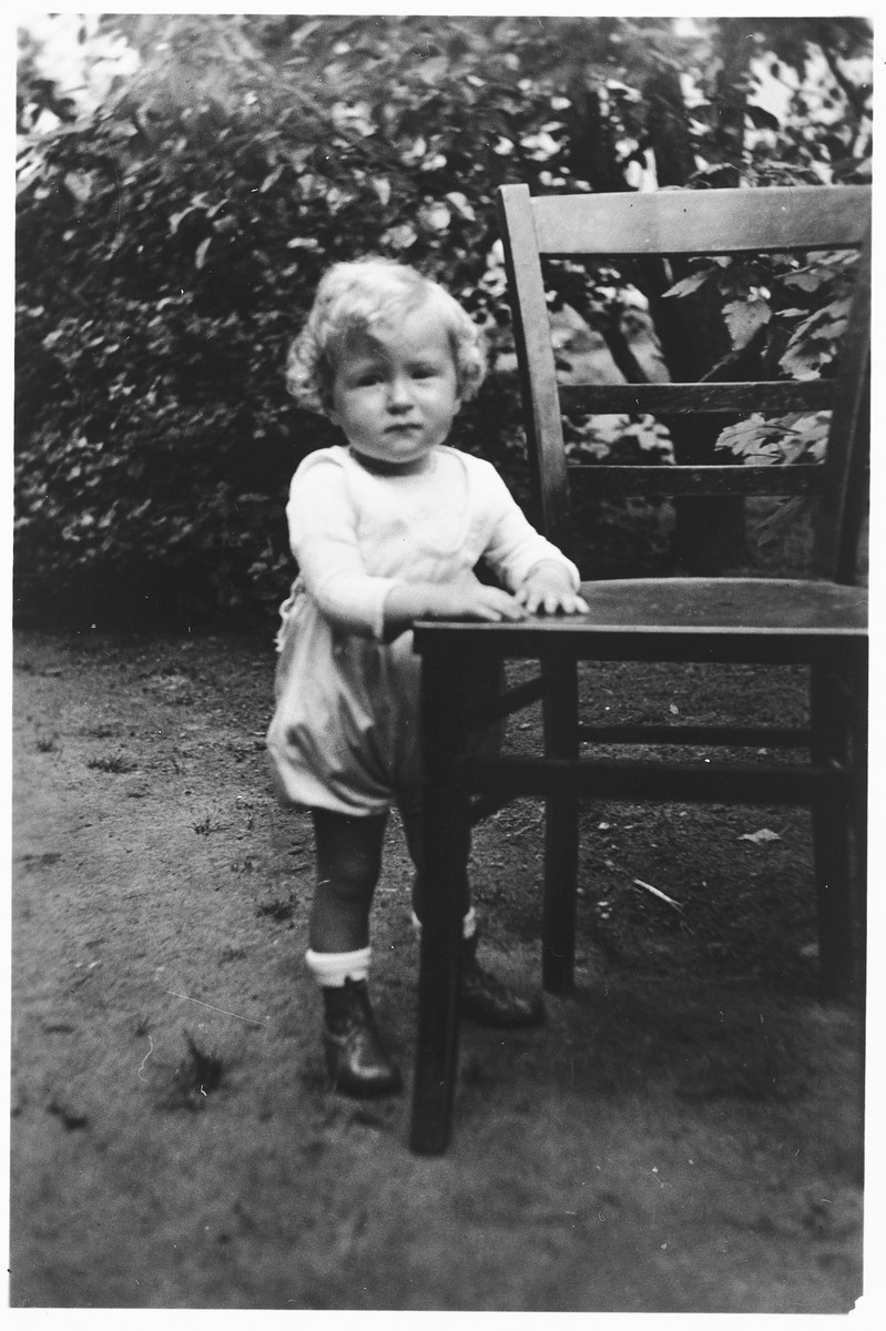 Portrait of a Jewish toddler holding onto a chair in the garden of a home in Frankfurt am Main, Germany.  Pictured is one-year-old Brigitte Joseph.