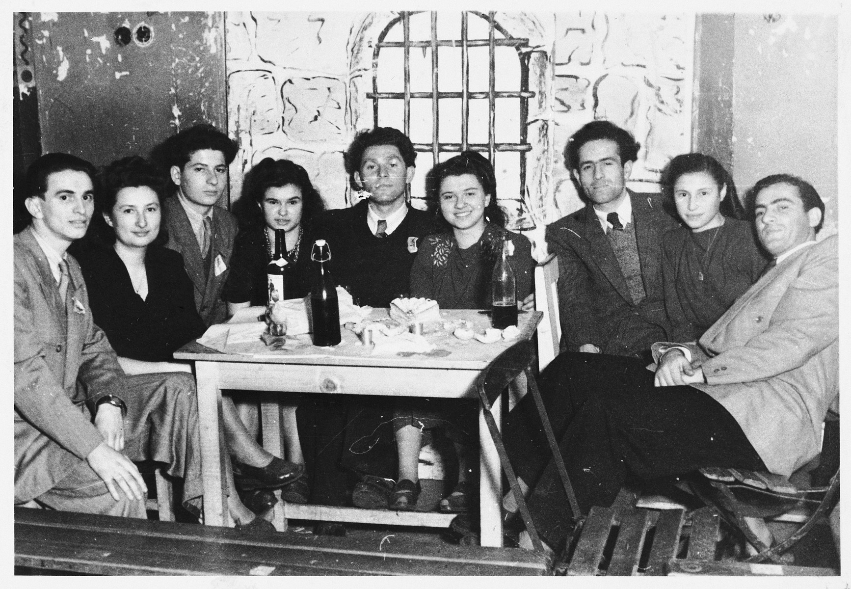 Jewish DP youth are gathered around a table with cake and wine in the Gabersee DP camp.  Among those pictured are David Wincygster (third from the right), Helen Spielman (fourth from the left), and her brother Arthur Spielman (far left).