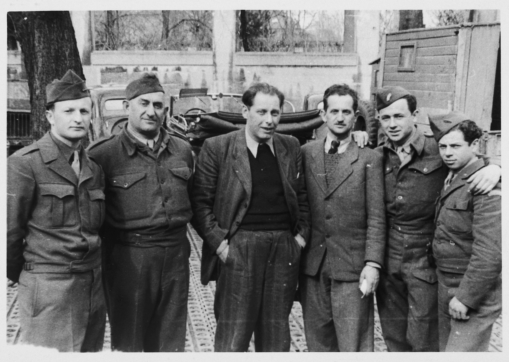 Group portrait of JDC employees at a warehouse in Munich.  Pictured from left to right are: Wolf Leizerowitz, Alte Berger, Isroel Ipp, Spilka, unidentified and Loke Karklin.