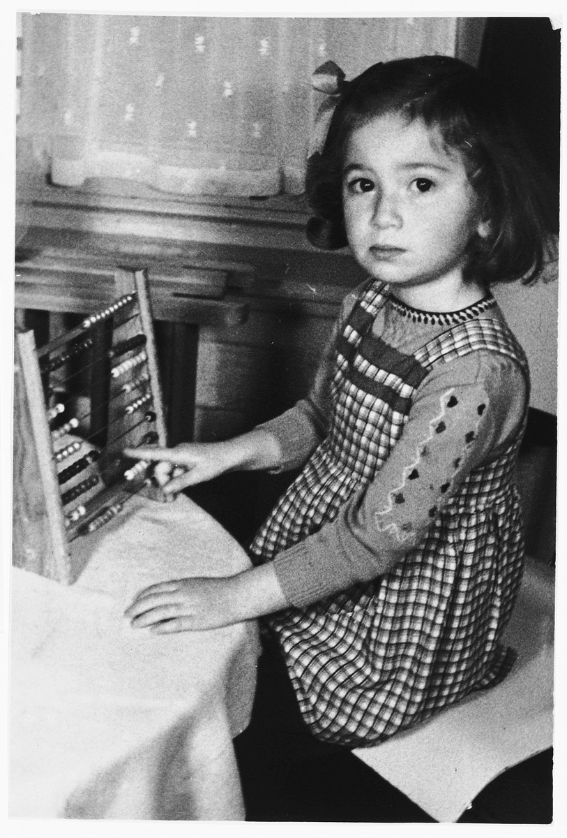 A young Jewish girl, Truusje Schoenfeld, plays with an abacus while living in hiding in The Netherlands.