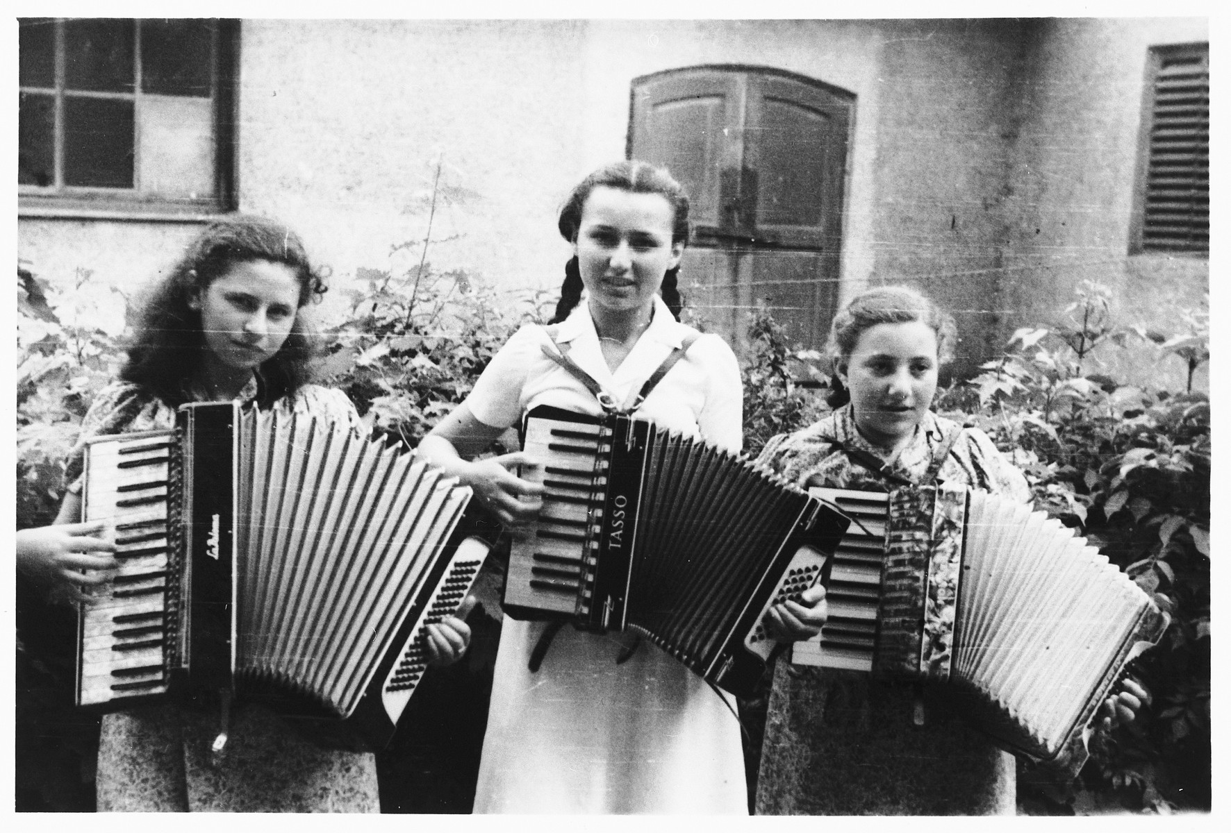 Three teenage Jewish girls play the accordian in the Gabersee displaced persons camp.  Pictured on the left is Rachel.  Selma is in the center.