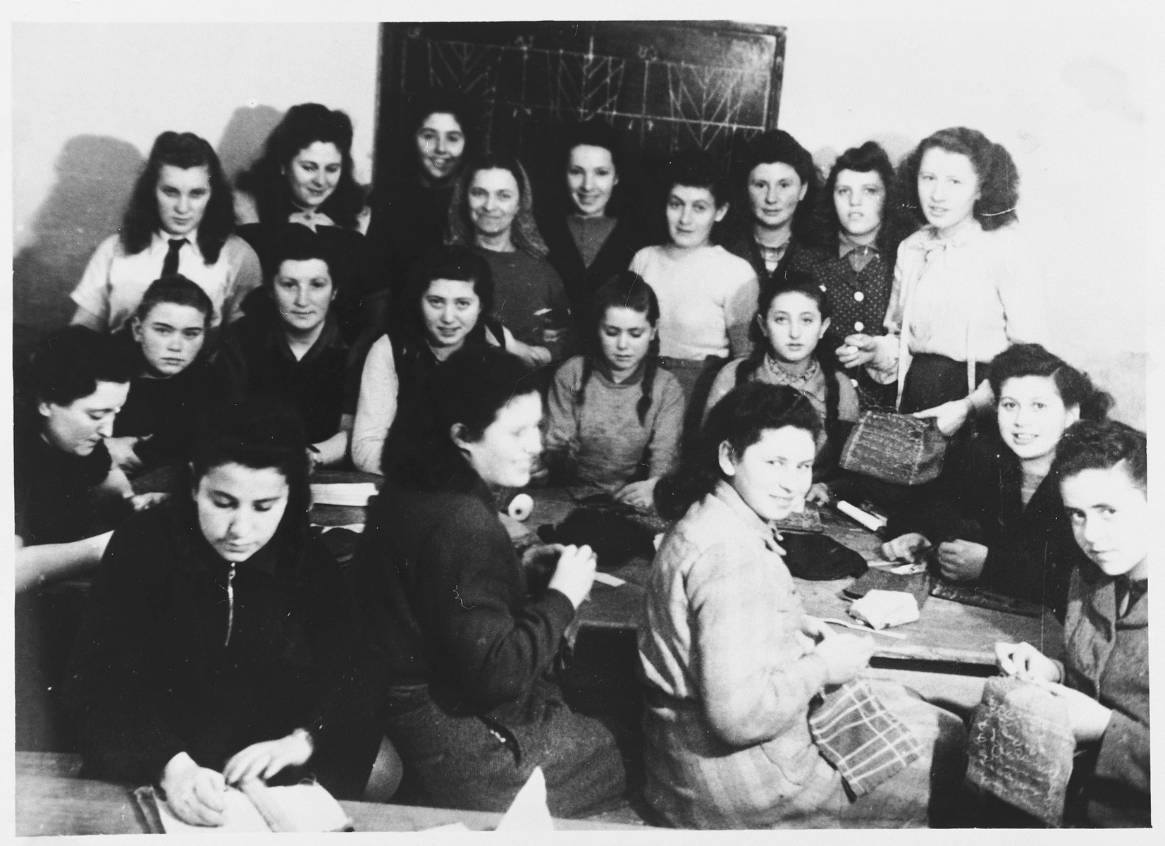 Teenage girls practice sewing in a vocational training class at the Gabersee displaced persons camp.  Among those pictured is Henia Spielman.