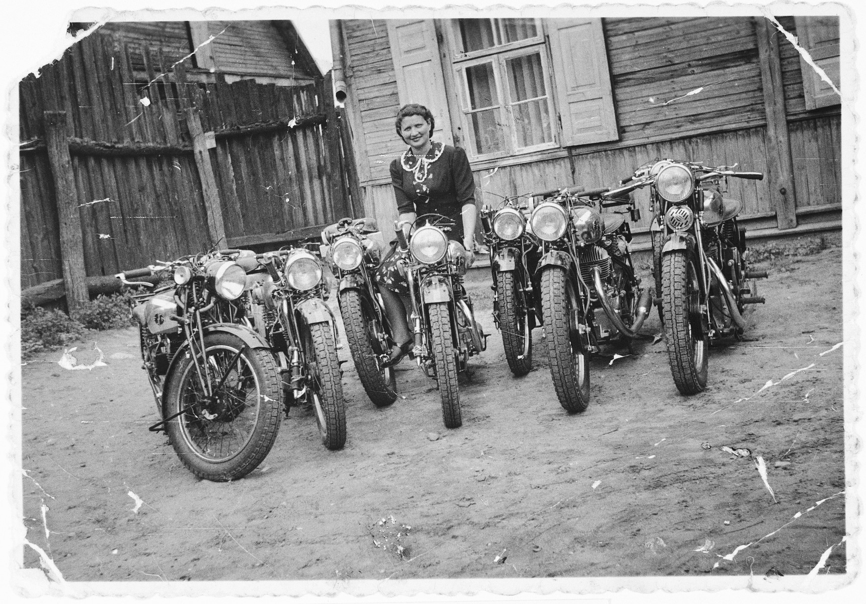 A young Jewish woman poses with her husband's inventory of motorcycles in Kaunas, Lithuania.  Pictured is Eta Ipp in front of the home of her father-in-law, Priedel Ipp.