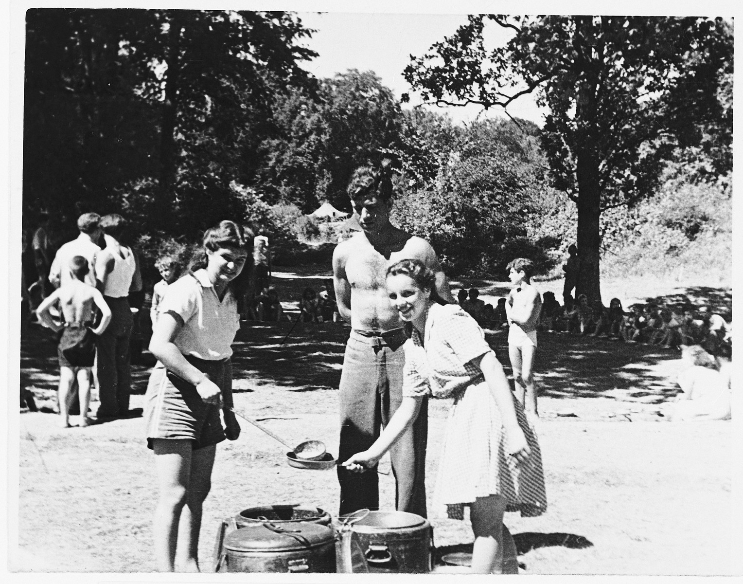 Henia Spielman (left) ladles out soup to two Jewish DP friends from the Gabersee DP camp during an outing in the woods.