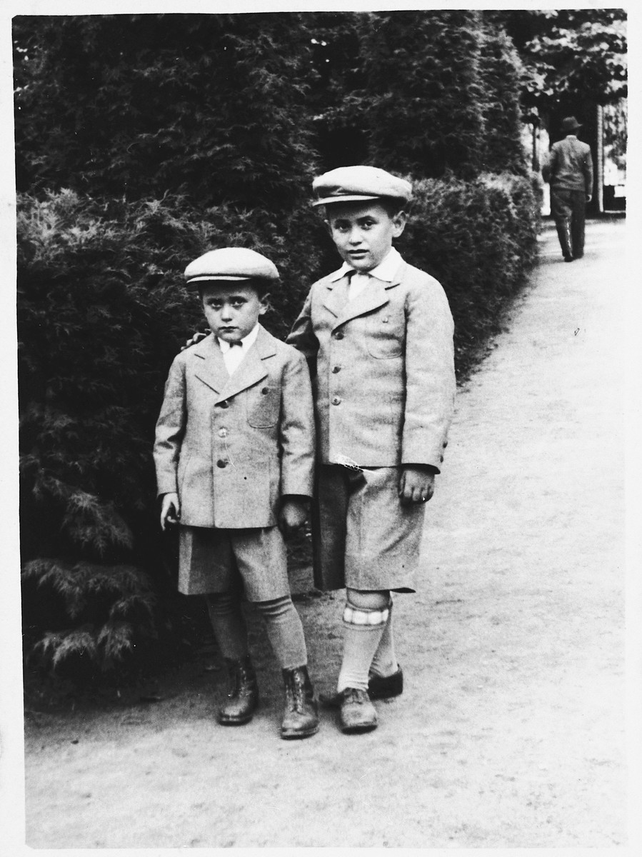 Two young Jewish brothers wearing matching suits and caps pose next to a hedge in Jaroslaw, Poland.  Pictured are Maurice and Shimon Friedberg.