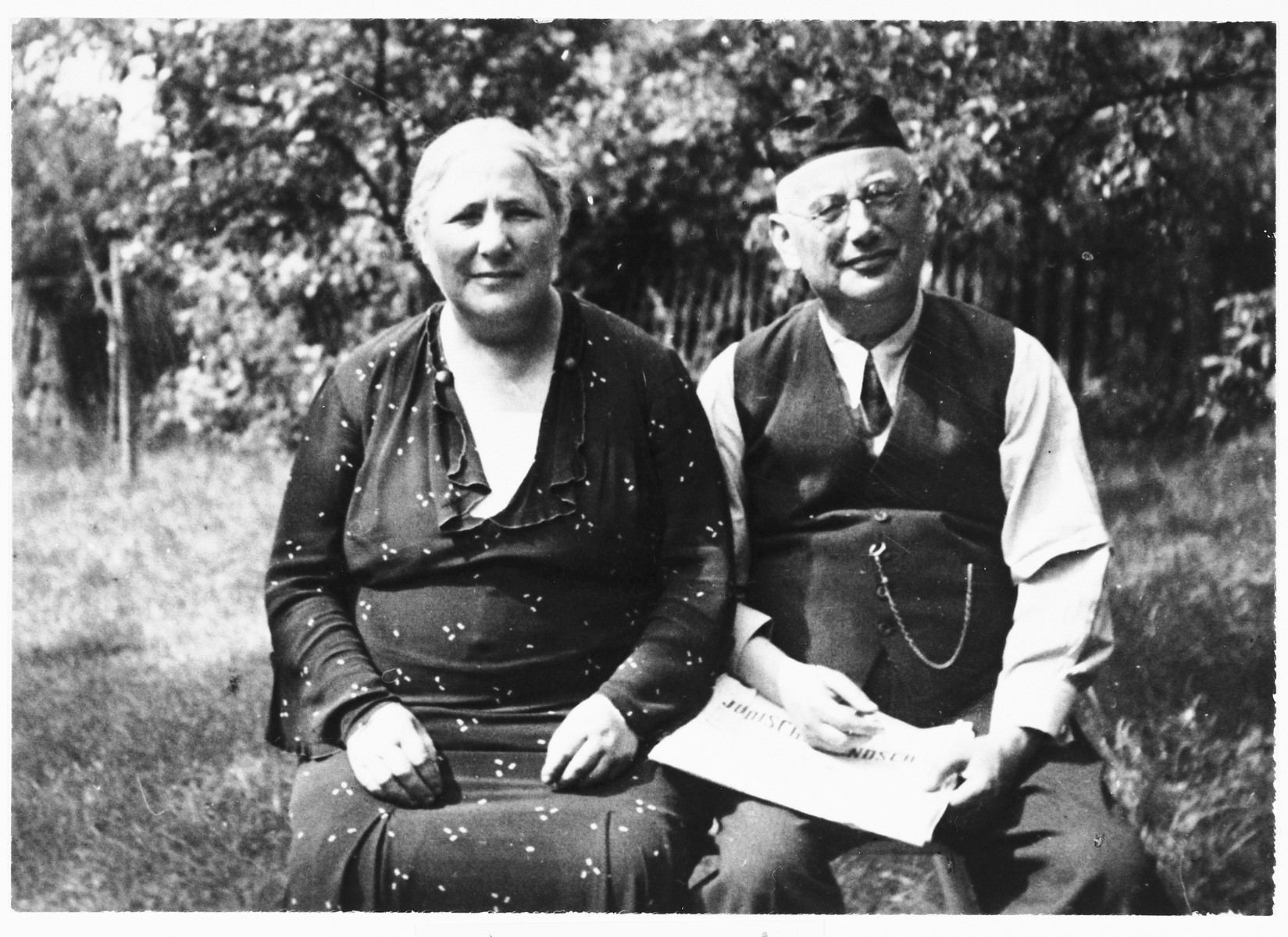 An elderly Jewish couple sits outside in their yard in Ottweiler, Germany.  Pictured are Levi and Bertha Katz.