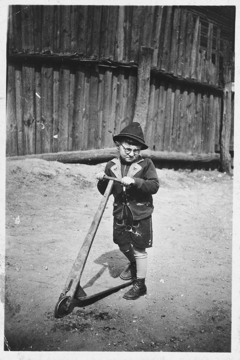 A young Jewish boy poses on his scooter near his home in Kaunas, Lithuania.  Pictured is four-year-old Yacob Ipp.