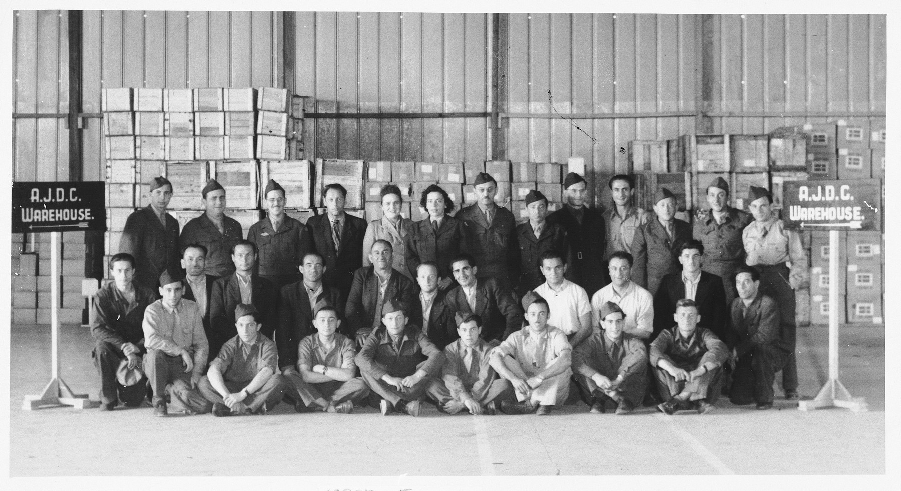 Group portrait of JDC employees at a warehouse in Munich.  Pictured in the front row: Loke Karklin (fourth from the left) and S. Kadosewitz (fifth from the left).  Middle row, left to right: unidentified, Dreicez, Zigelbaum, A. Berger, Leizerowitz, R. Willonsky, Israel Gillman, unidentified, S. Mozeshow, and Karklin.  Back row: Isroel Ipp (third from the left), Ira Jochelson (seventh from the left), S. Kochman (ninth from the left), and A. Kochman (eleventh from the left).