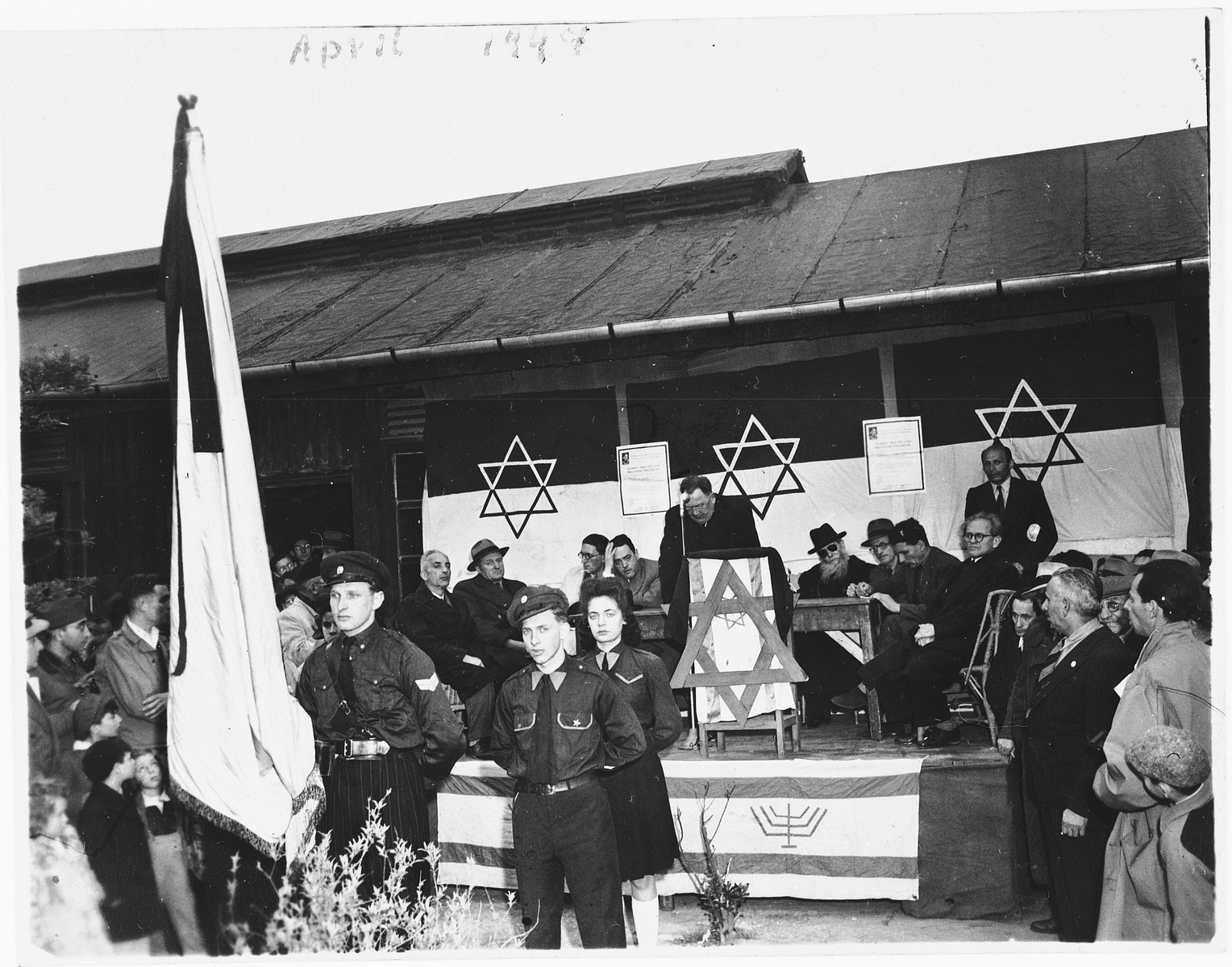 Members of the Betar youth movement stand at attention with a flag in front of the stage during a community Zionist gathering.
