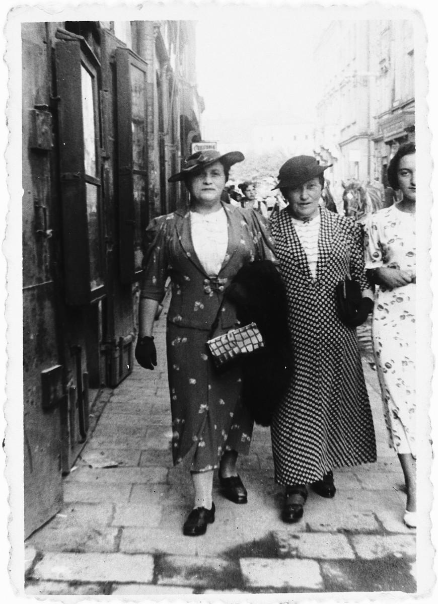 Three Jewish women walk along a commercial street in Rzeszow, Poland.  Pictured are Memel Jan (center) with her two daughter, Ida (Jam) Friedberg (left) and Dola (Jam) Tannenbaum (right).