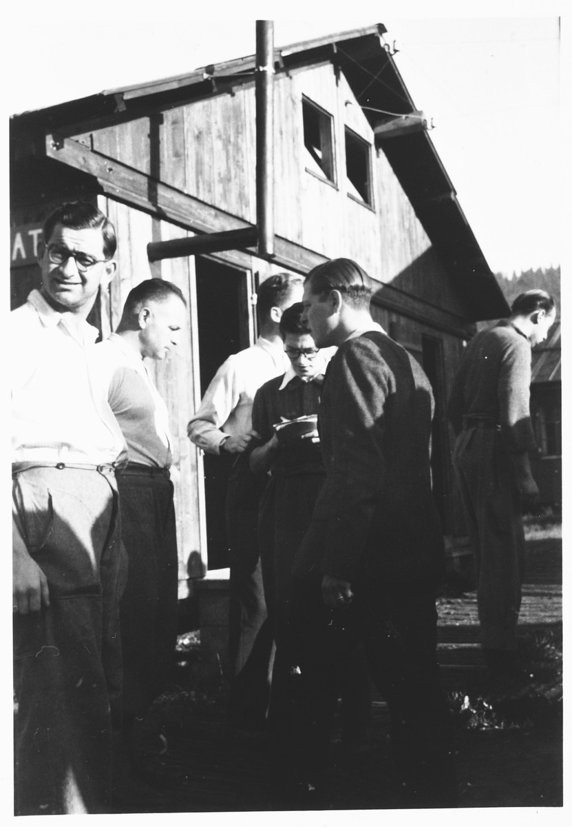 Refugees gather outside a barracks in an internment camp in Cossonay, Switzerland.  Most of the internees were Dutch Jews.  Capt. Bachmann (Swiss) is on the left and Bachrach is on the right.
