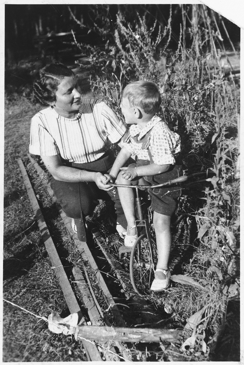 A young Jewish mother helps her son ride a tricycle in the resort town of Kulautuva, Lithuania.  Pictured are Eta and Yacob Ipp.