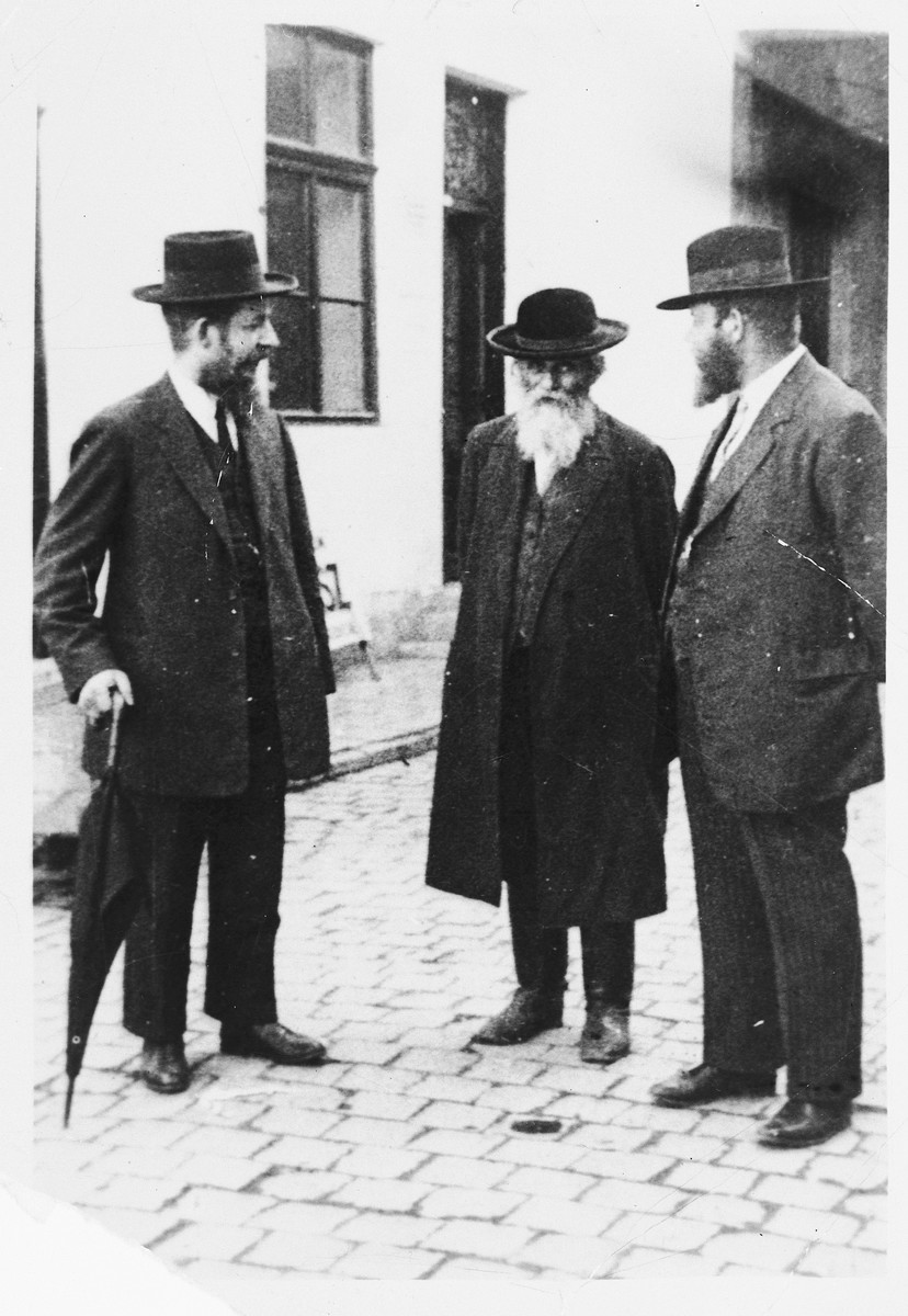 Three religious Jews converse on a street corner in Mukachevo.  Pictured are Chaim Shlomo Grunberger (center) and his sons, Eliahu and Shmuel.