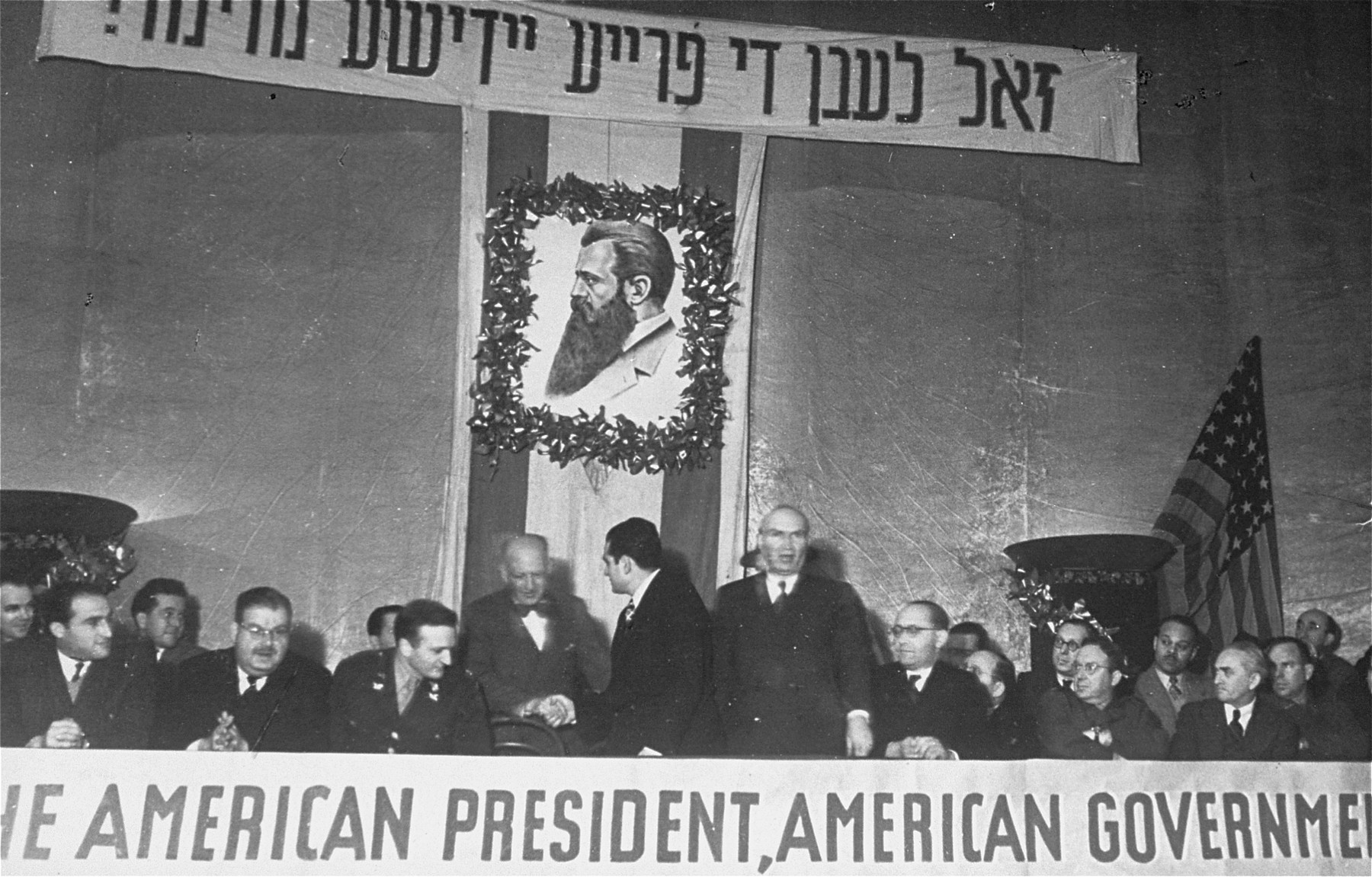 Members of the Central Committee of Liberated Jews in the U.S. Zone of Germany attend a meeting in the Prinzregenten Theater celebrating the partition of Palestine.    David Treger, chairman of the committee, stands in the center, facing the camera.