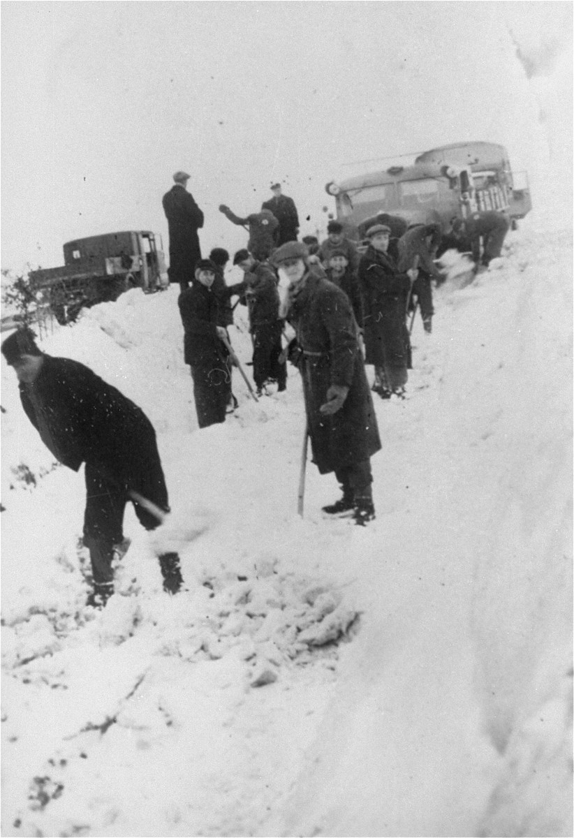 Jewish forced laborers from the Klettendorf labor camp shovel snow in preparation for the construction of the new autobahn between Breslau and Berlin.    Jacob Hennenberg stands in front at the right.  The photograph was taken by a German guard who sent it to Jacob's sister in the Chrzarnow ghetto.