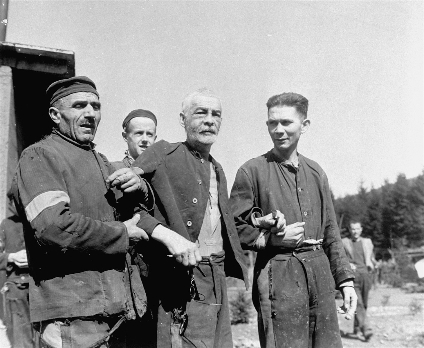 Two fellow prisoners support a weak and elderly Jewish man in the concentration camp at Holzen, Germany. These prisoners, subject to starvation, beatings, and disease, were liberated by units of the 9th U.S. Army.