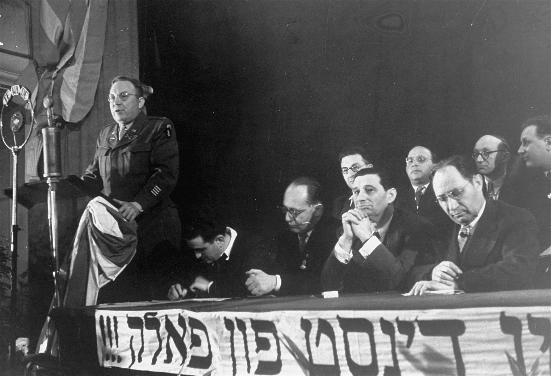 Honored guests seated on the dais listen to a speech at the Third Conference of Liberated Jews in the US Zone of Germany.  Joseph Schwartz is pictured in the front row, second from right.
